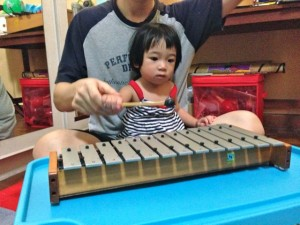 Coco learning about music tones on the xylophone