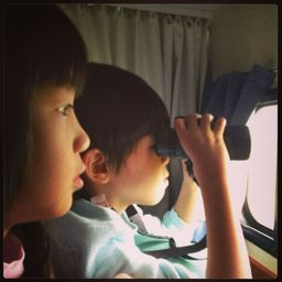 Jairus and Kristen , in their pj's , at the window of our campervan looking out at ....