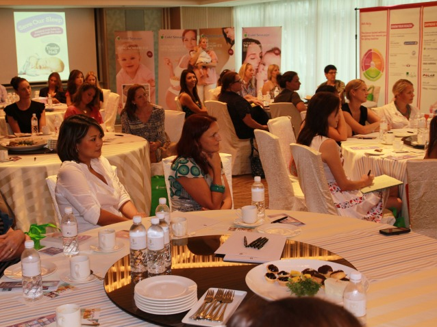 Members of the audience attentively listening to personalised advice for sleep-deprived moms