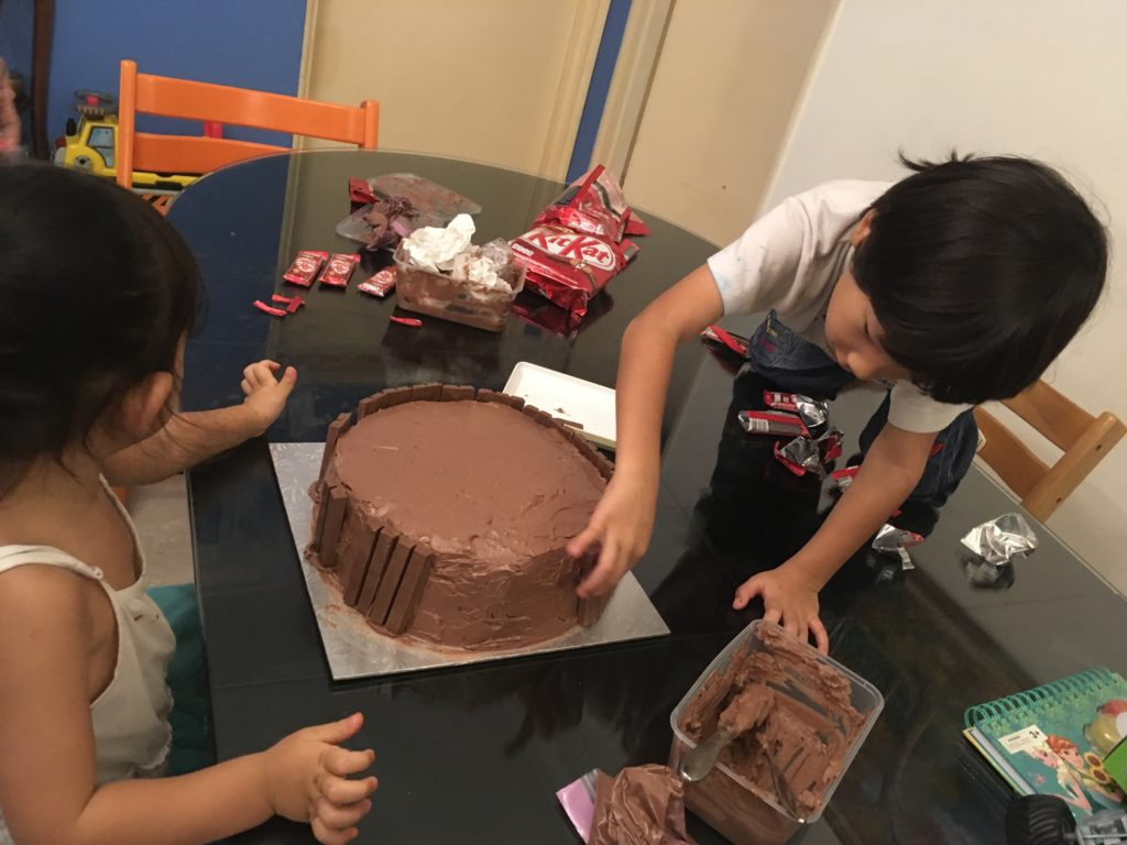 Sticking the Kit Kat fingers on the side of the cake